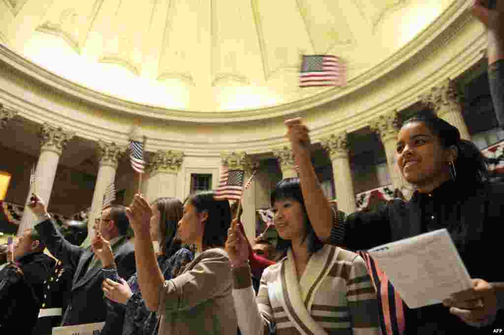 Candidates from 40 countries wave flags after they were naturalized as U.S. citizens in a ceremony at Federal Hall in New York.