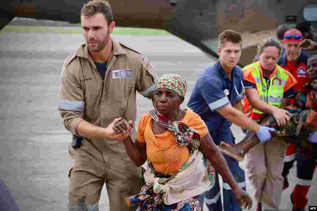 Pessoas são ajudadas no aeroporto da cidade da Beira, no centro de Moçambique, a 19 de Março, 2019, depois da região ter sido afectada pelo ciclone Idai