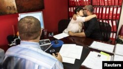 Michal (C) and Shay (R) kiss after signing a marriage agreement, not recognized as valid by Israel's Interior Ministry, in front of a lawyer at an organization providing family law services, in Tel Aviv, Nov. 19, 2013.