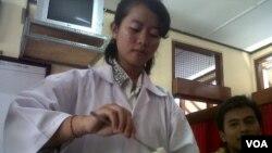 Gusti Ayu Indah Lestari, pelajar SMUN 3 Denpasar, didampingi gurunya saat melakukan praktikum di laboratorium di sekolah (Foto: VOA/Muliarta).