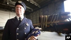 Bob McGovern, with the St. James, N.Y. Fire Department, holds the American Flag while waiting for a piece of steel to be loaded on a flatbed truck at John F. Kennedy International Airport, June 16, 2011 in New York.