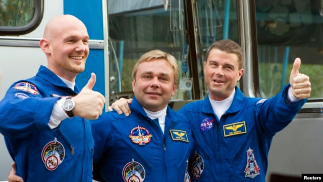 The International Space Station (ISS) crew members (L-R) Alexander Gerst of Germany, Maxim Surayev of Russia and Reid Wiseman of the U.S. pose before going from a hotel for a final pre-launch preparation at the Baikonur cosmodrome, May 28, 2014.