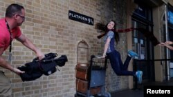 A woman poses for a photograph with the Harry Potter trolley at Kings Cross Station, in London, Britain, June 26, 2017.