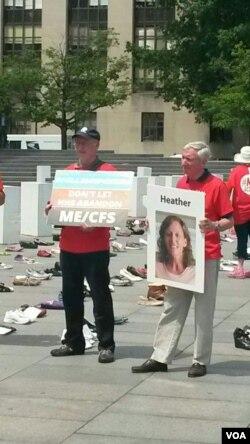 抗议者手握标语牌和患病家人的照片。(美国之音乔栈拍摄)