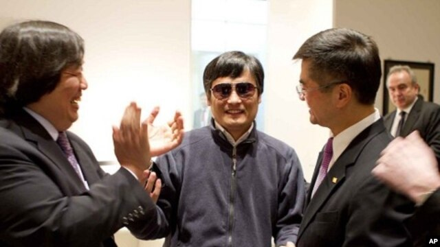 In this photo released by the US Embassy Beijing Press Office, blind lawyer Chen Guangcheng, center, holds hands with U.S. Ambassador to China Gary Locke, right, as U.S. State Department Legal Advisor Harold Koh, left, applauds, before leaving the U.S. em