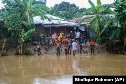 Rohingya refugees look at flood water following heavy rains at the Rohingya refugee camp in Kutupalong, Bangladesh, Wednesday, July 28, 2021.