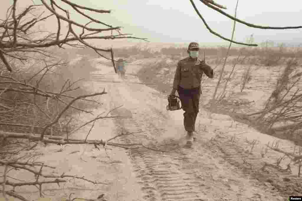 Seorang polisi berjalan melewati debu dalam operasi penyelamatan setelah letusan Gunung Sinabung, dekat desa Suka Meriah di Karo, Sumatera Utara 2 Februari 2014.