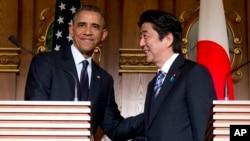 រូបឯកសារ៖ លោកប្រធានាធិបតី Barack Obama និងនាយករដ្ឋមន្ត្រីជប៉ុន លោក Shinzo Abe ចាប់ដៃគ្នានៅចុងបញ្ចប់នៃសន្និសីទកាសែតរួមមួយនៅគេហដ្ឋានសម្រាប់ទទួលភ្ញៀវរបស់រដ្ឋ Akasaka នៅក្រុងតូក្យូ ថ្ងៃទី២៤ ខែមេសា ឆ្នាំ២០១៤។ (AP Photo/Carolyn Kaster)