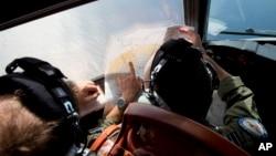Pilotos australianos ven un mapa de la nueva área de búsqueda, mientras buscan sobre el Océano Indico, a bordo de un avión Orión AP-3C.