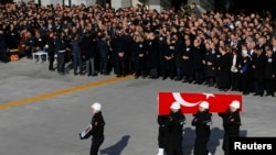 Turkish police officers carry a coffin of a fellow officer during a ceremony for police officers killed in Saturday's blasts in Istanbul, Dec. 11, 2016.