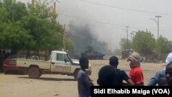 Quelques personnes regardent au loin le lieu d'une attaque-kamikaze dans la région de Gao, dans le centre-nord du Mali, 1er juillet 2018. (VOA/ Sidi Elhabib Maiga)