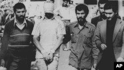 1979年11月9日,劫持美國外交官的伊朗人在美國駐德黑蘭大使館外將一名美國人質蒙面綁手示眾。 (資料圖片)