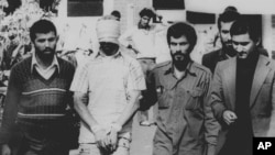 FILE - An American hostage is paraded before a crowd outside the U.S. Embassy in Tehran on Nov. 9, 1979.