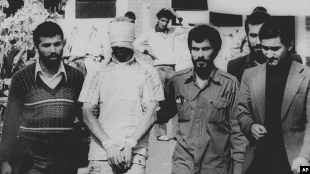 FILE - One of 60 U.S. hostages, blindfolded and with his hands bound, is being displayed to the crowd outside the U.S. Embassy in Tehran by Iranian hostage takers, Nov. 9, 1979.