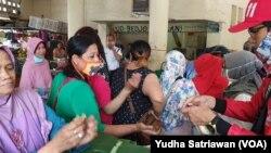 Relawan membagikan sabun cuci tangan kepada pedagang pasar Gedhe Solo, 21 Maret 2020. (Foto: VOA/ Yudha Satriawan)