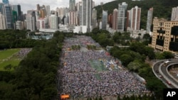 Tens of thousands of residents gather to march in downtown streets during an annual pro-democracy protest in Hong Kong Tuesday, July 1, 2014. Hong Kong residents began marching through the streets of the former British colony to push for greater democracy