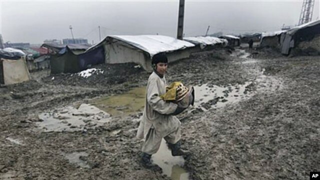 An Afghan boy from a poor neighborhood carries bread on his way home as it rains in Kabul, Afghanistan, February 23, 2011