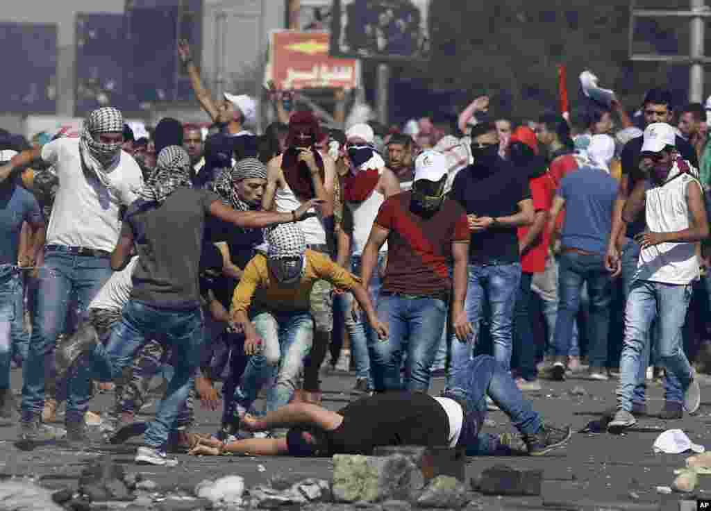 An injured Palestinian demonstrator is helped during clashes at the Hawara checkpoint near of the West Bank city of Nablus. At least 45 Palestinians were wounded by live bullets in clashes between university students and Israeli forces at the military checkpoint near Nablus, the Palestinian Health Ministry said.