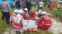 Personel Palang Merah Indonesia (PMI) melakukan evakuasi dan perawatan korban dalam kegiatan simulasi darurat bencana banjir bandang dan gempa bumi di Sigi, Sulawesi Tengah, pada 27 Oktober 2021. (Foto: VOA/Yoanes Litha)