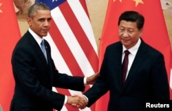 U.S. President Barack Obama shakes hands with China's President Xi Jinping in front of U.S. and Chinese national flags during a joint news conference at the Great Hall of the People in Beijing, Nov. 12, 2014.
