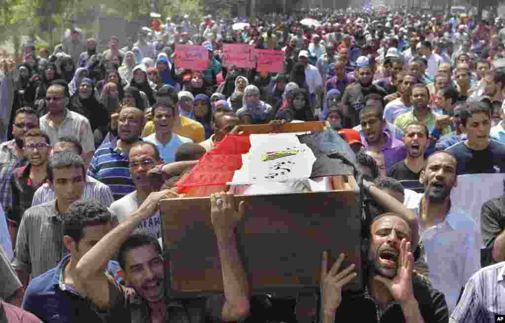 Supporters of Egypt's ousted President Mohamed Morsi carry a coffin, covered with a national flag, of a protester who was killed during Wednesday' clashes in Cairo, August 16, 2013.