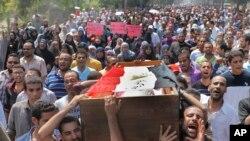 Pendukung Morsi (16/8) mengusung peti mati salah seorang demonstran yang tewas dalam penghancuran kamp-kamp demonstran oleh pemerintah Mesir hari Rabu.