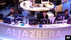 FILE - Al Jazeera English Channel staff prepare for the broadcast in Doha news room in Qatar.