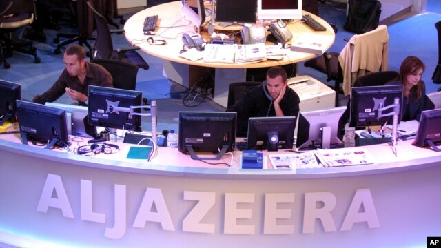 FILE - Al Jazeera English Channel staff prepare for the broadcast in Doha news room in Qatar.