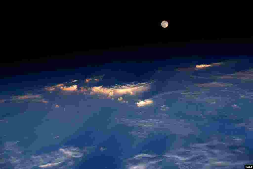 "Expedition 48 Commander Jeff Williams of NASA took this photograph from the International Space Station. He wrote, ""A spectacular rise of the full moon just before sunset while flying over western China."""