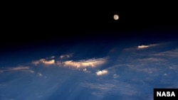 "FILE - Expedition 48 Commander Jeff Williams of NASA took this photograph on June 21, 2016, from the International Space Station, writing, ""A spectacular rise of the full moon just before sunset while flying over western China."""