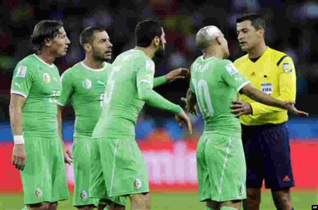 Algeria's Sofiane Feghouli (10) and his teammates plead their case with referee Sandro Ricci from Brazil during the World Cup round of 16 soccer match between Germany and Algeria at the Estadio Beira-Rio in Porto Alegre, Brazil, Monday, June 30, 2014. (AP