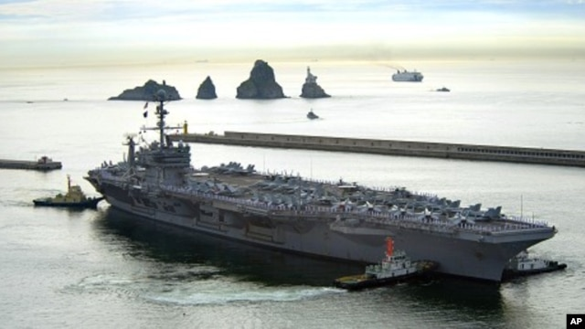 The aircraft carrier USS George Washington (CVN 73) departs Busan, Republic of Korea, 25 July 2010