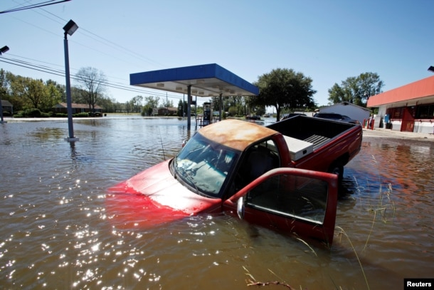 FILE - An abandoned truck lies in submerged waters after Hurricane Matthew hit Lumberton, North Carolina, Oct. 9, 2016.