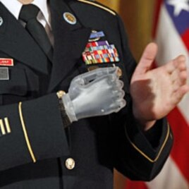 With his prosthetic hand, U.S. Army Sergeant First Class Leroy Arthur Petry applauds fellow soldiers during a ceremony in which he was presented with the Medal of Honor by U.S. President Barack Obama at the White House, July 12, 2011