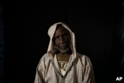 FILE - Cheikh Fofana poses for a picture before an interview in Goudiry, Senegal, Nov. 26, 2018. Fofana grieves his son, Tidiane's absence, even while refusing to officially acknowledge he is dead.