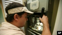 FILE - A home inspector checks air-conditioning coils at a home in the Kendall suburb of Miami.