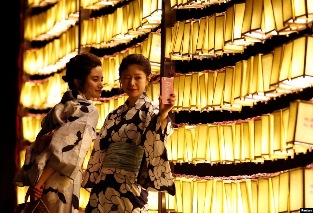 穿着夏季和服的女子在东京的灯笼前自拍(2017年7月13日)。