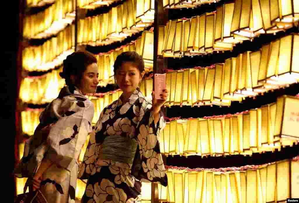 Dua perempuan mengenakan yukata, atau kimono santai musim panas, mengambil foto selfie di depan lentera kertas di kuil Yasukuni di Tokyo, Jepang.