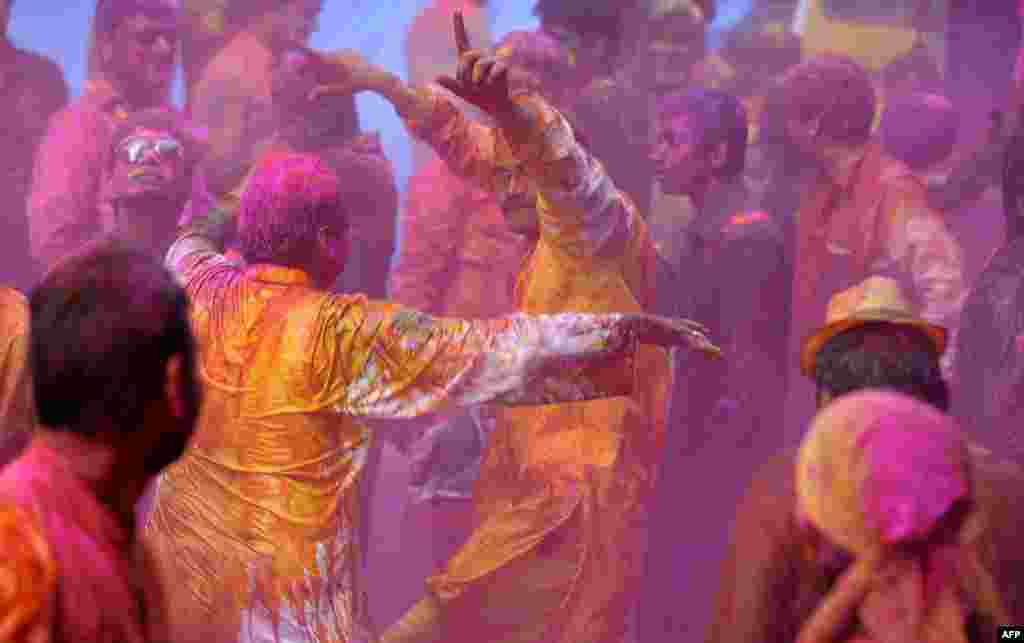 Indian people apply colored powder and dance during Holi celebrations in Hyderabad, India.