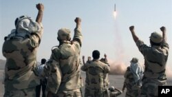 FILE - Members of the Iranian Revolutionary Guard celebrate after launching a missile during maneuvers in an undisclosed location in Iran, July 3, 2012.