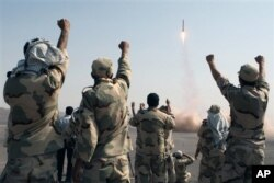 FILE - In this photo released by the Islamic Republic News Agency (IRNA), members of the Iranian Revolutionary Guard celebrate after launching a missile during their maneuver in an undisclosed location in Iran, July 3, 2012.