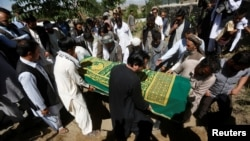 FILE - Afghans take part in the burial of an Afghan journalist in Kabul, Afghanistan, June 7, 2016. On Friday, a roadside bomb killed one journalist and wounded another. In Afghanistan, 2016 is the deadliest year yet for journalists.
