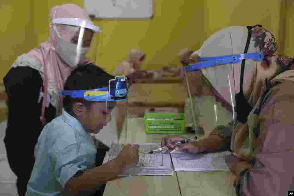 Teachers and students wear protective gear as a precaution against the new coronavirus outbreak during a class at a Quran educational facility at on the outskirts of Jakarta, Indonesia.