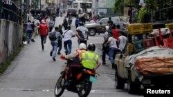La gente huía de la policía durante los disturbios en reclamo de alimentos en Caracas, Venezuela, el jueves, 2 de junio de 2016.