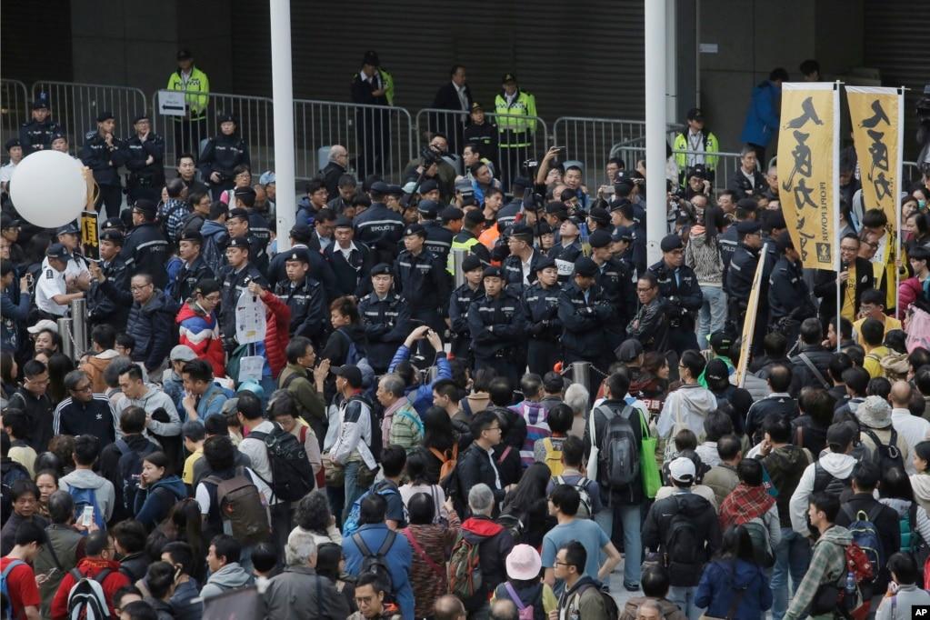 """2018年1月1日,香港政府總部外面有大批抗議者和警察。 示威者要求捍衛香港""""基本法""""和""""一國兩制""""。"""