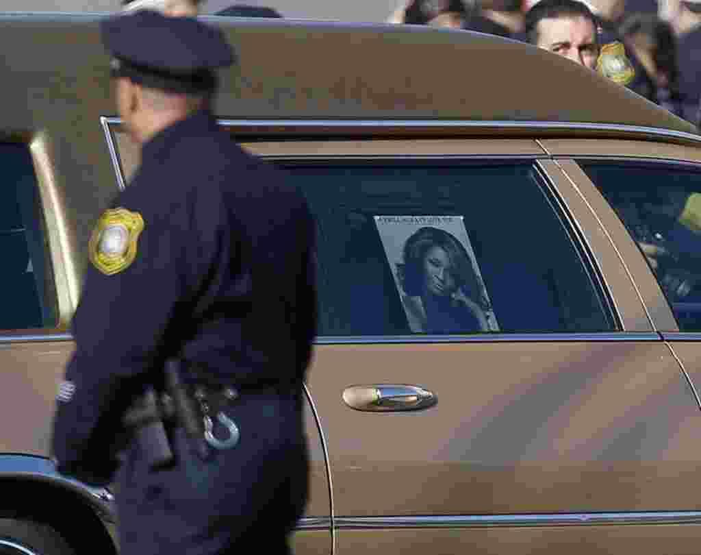 Seorang polisi Newark menyaksikan mobil jenazah Whitney Houston tiba di Gereja New Hope Baptist, New Jersey, 18 Februari 2012 (REUTERS).