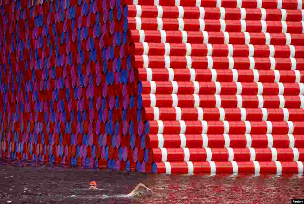 "Swimmers exercise in the Serpentine River in front of Christo's ""The London Mastaba"", in Hyde Park, London."