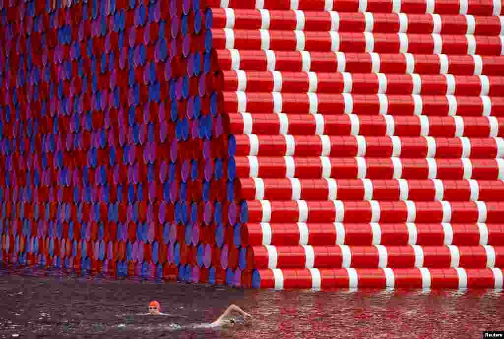 កីឡាករហែលទឹកកំពុងហាត់នៅទន្លេ Serpentine Riverខាងមុខរូបសំណាក «The London Mastaba» ក្នុងសួន Hyde Park ទីក្រុងឡុងដ៍។