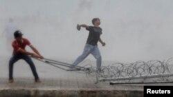 Para aktivis oposisi di Phnom Penh, Kamboja melemparkan batu ke arah polisi dan berusaha menyingkirkan barikade dalam protes yang rusuh hari Minggu (15/9).
