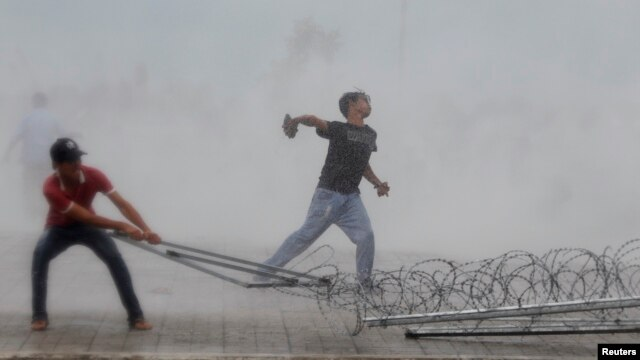 A protester supporting the opposition Cambodia National Rescue Party (CNRP) throws a stone as another tries to remove barbed wire barricades during clashes with police officers near the Royal Palace in central Phnom Penh Sep. 15, 2013.